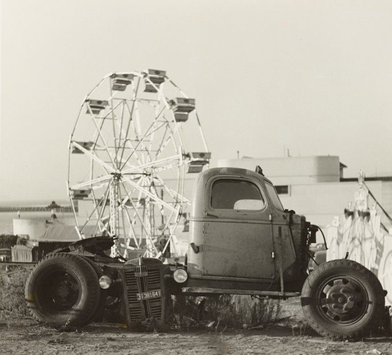 old truck with front end missing; grill with headlights leaning against back of truck in front of back tire; Ferris wheel visible behind truck