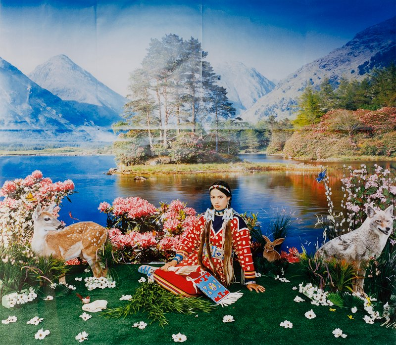 Native American woman in traditional dress kneels on floor surrounded by artificial and natural props: white flowers scattered on green turf, young deer at left, coyote at right, pink flowers, butterfly; lake and mountains as backdrop