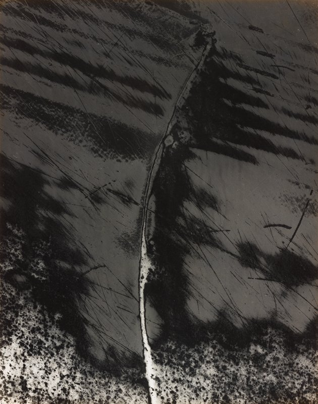 abstract image; black and white mottled areas at bottom; vertical linear form at center; grey and black ground