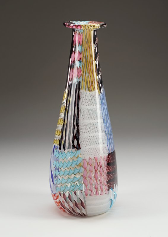 elongated vase with roughly triangular shaped lower body; long rounded neck with outward-flaring flat rim; clear glass with patchwork of twisted glass in various multicolored patterns