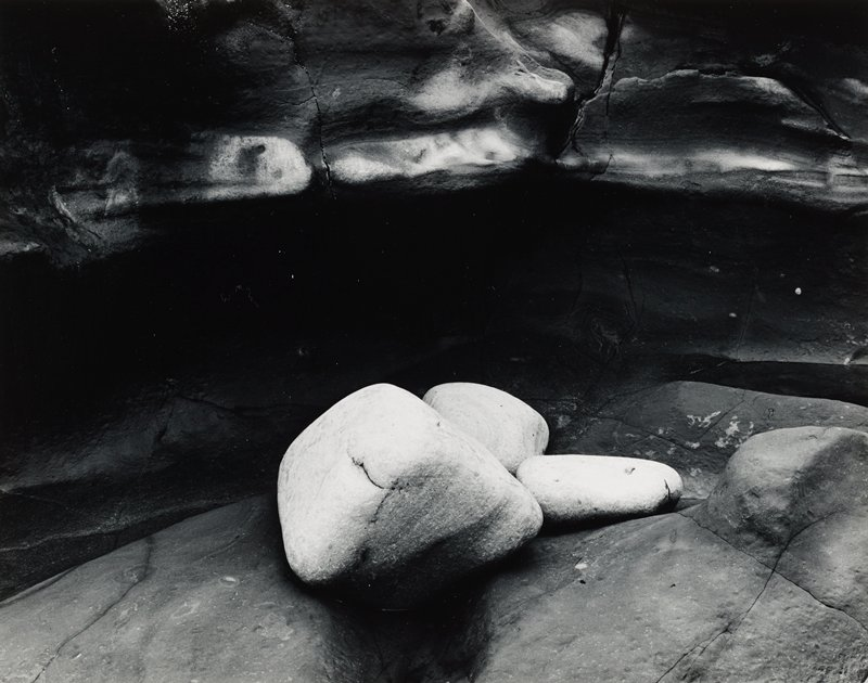 three smooth light-colored stones resting together on darker stones, with similar dark rock wall in background
