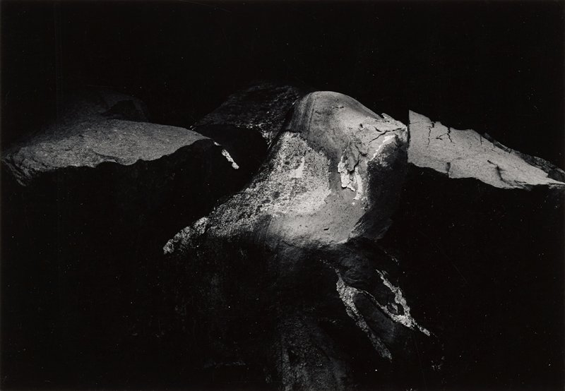 abstract image; rock formation against dark black ground