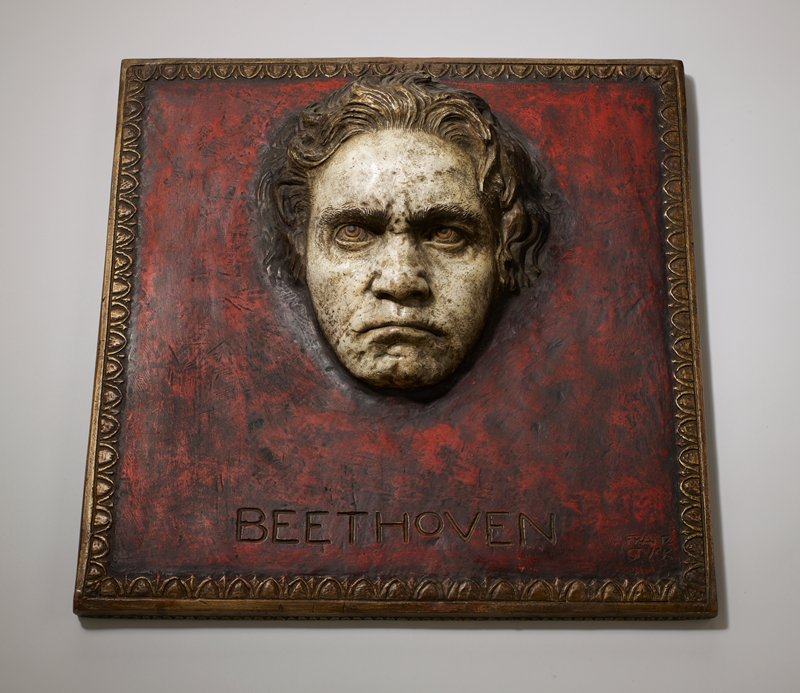 "high relief plaque with head of Beethoven emerging from dark red ground; egg and dart motif around edges of panel; ""BEETHOVEN"" incised at bottom; skin is pale white; brown eyes and light brown hair; scowling expression"