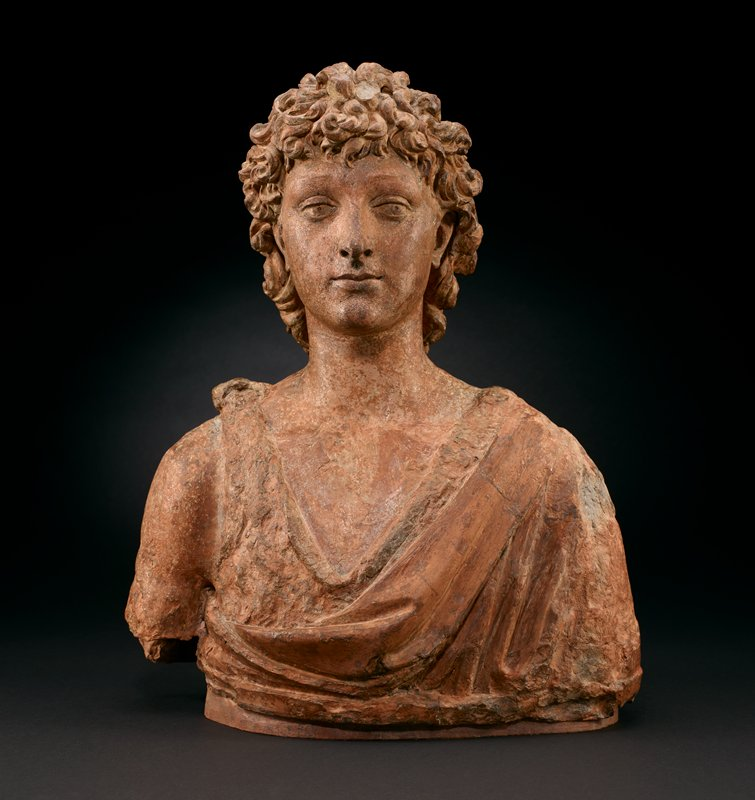 bust of young man with medium-length curly hair; man wears draping garment with low neckline with knot on PR shoulder; bare PR arm; mottled patina