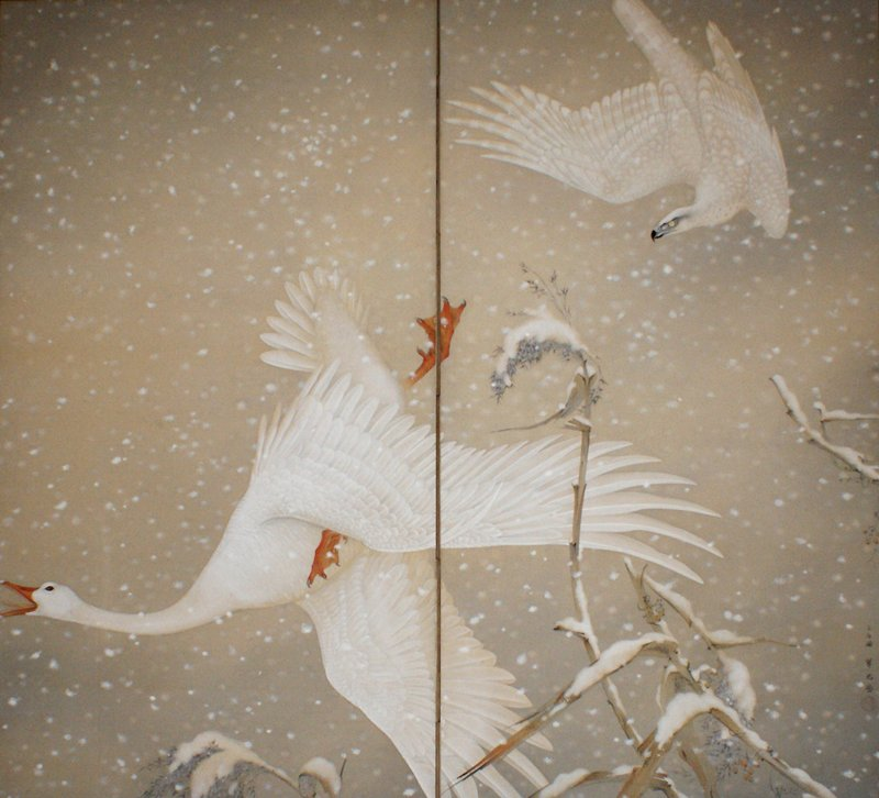 white falcon at UR in twisting dive after large white goose at center; goose is lunging downward with legs splayed and mouth wide open; large clumps of fluffy snow fill scene; snow-covered foliage at bottom