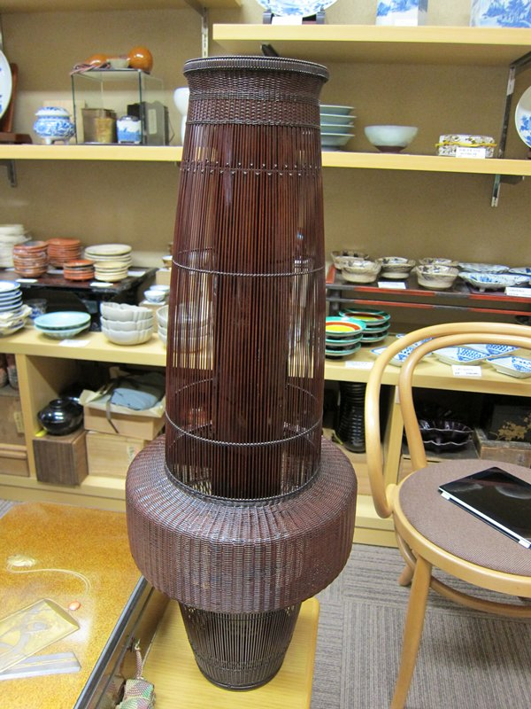 tall, open weave vase in three attached segments; top cylinder widens slightly on descent; wide, bulbous, tightly woven center segment; bottom segment similar cylindrical shape, tapering slightly towards bottom; tight, decorative weave at top and bottom edges; dark bamboo inner cylinder