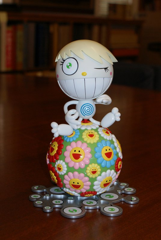 small white plastic figure with large head, blonde hair, two mouths, and many green eyes sits in meditation position atop a green plastic orb covered with brightly colored flowers, each smiling at the center; orb comes apart revealing small CD supported on white base with blue swirl; underside of top of orb is decorated with white lotus with eyeball at center; sits on silver base with eyeballs