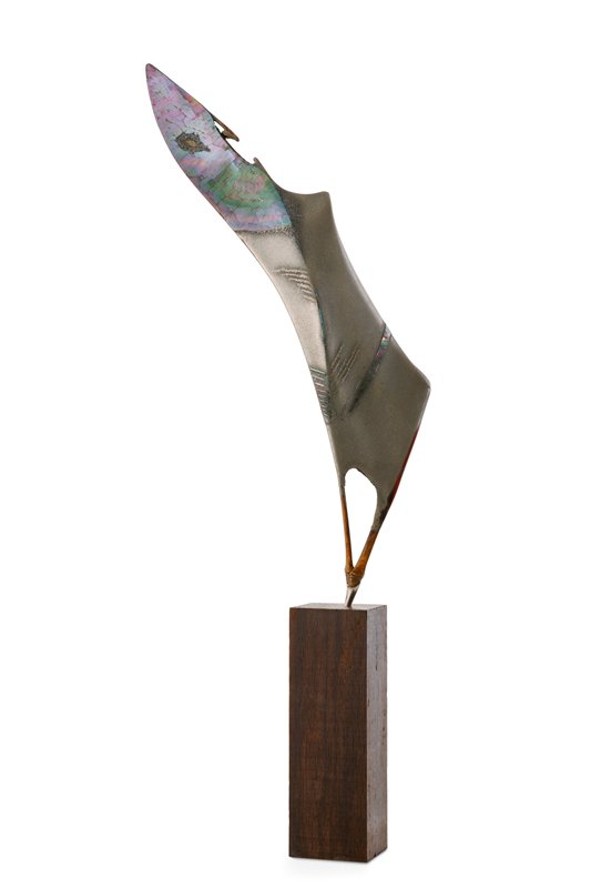 abstract leaf like form with mother-of-pearl inlay at top and near bottom; opposite side resembles bat wing; attaches to small rectangular wooden base