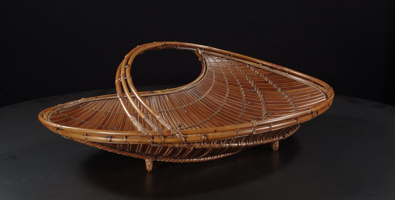 flat, kidney-shaped basket with slightly pointed end; low handle arcing over basket between pointed end and rounded end; vertical weave alternating between wide and thin slats with spiraled horizontal stitching; low lacquered bamboo cylinder
