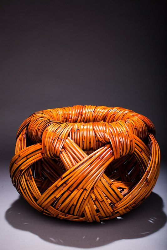 large open weave basket with rounded form; thick, crisscrossing strips of bamboo, with large holes; wide, broad mouth; dark cherry stained water container