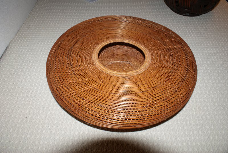 round basket with flat top and round mouth; star-patterned weave with spiraling top weave; hexagonal base; wide bamboo cylinder for holding flowers