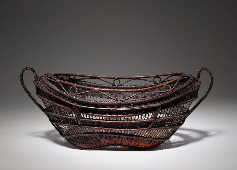 "oval basket with subtle feet; alternating ridges of open and closed weaving; looping design within inner lip; two curved ""teacup"" like handles"