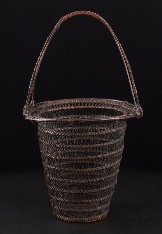 round, high-sided basket with taper towards bottom; looping, open weave anchored by concentric rings; wide lip with loops; handle with three strips adjoining at top