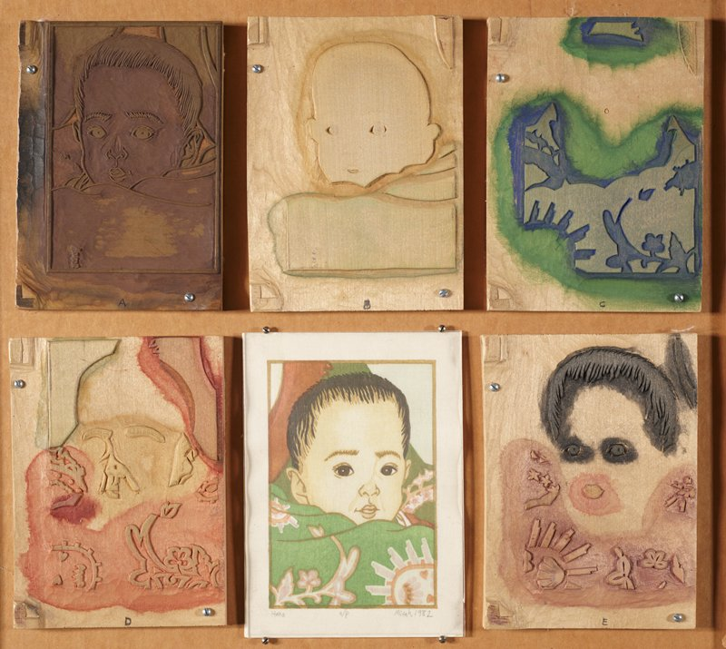 five carved wooden blocks, each with a different stage of woodblock print process; blocks mounted to wooden frame; at bottom center is the finished print of a baby's face enveloped in its mothers arms; mother is wearing green kimono with pink and white motif