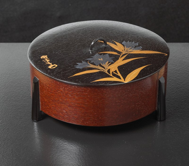 round box with black lid painted with a cluster of silver and gold violets; wood grain sides; black lacquered feet