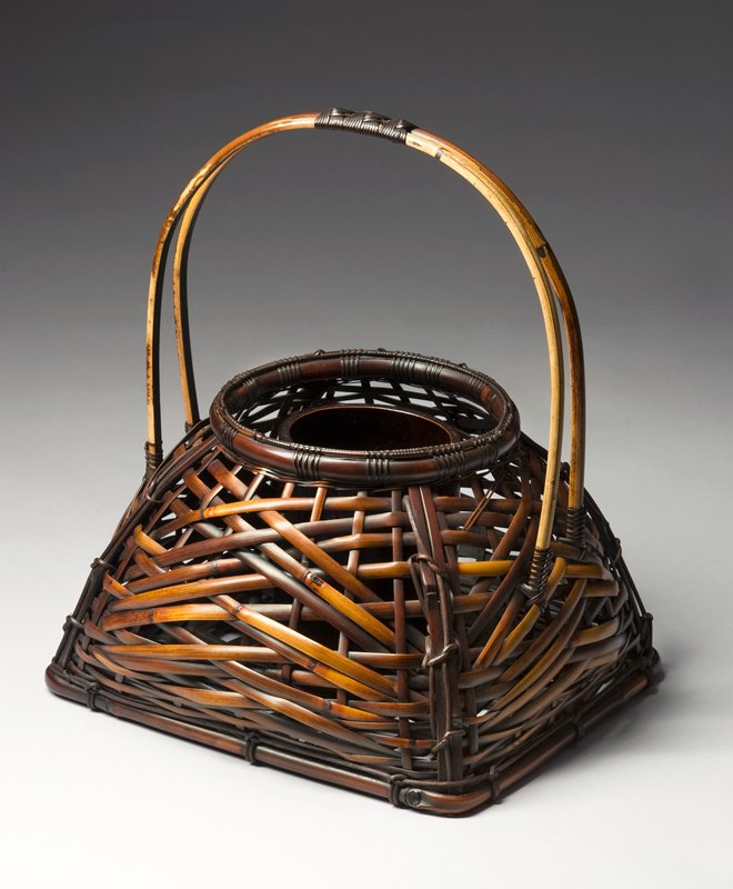 short, squat four-cornered basket tapering to narrower top with round opening; sides curve outward; handle formed from two bamboo branches that match the width of the basket; secured at top center with three decorative knots; open, crisscross weave with relatively wide bamboo strips; center flower cylinder dark lacquered bamboo