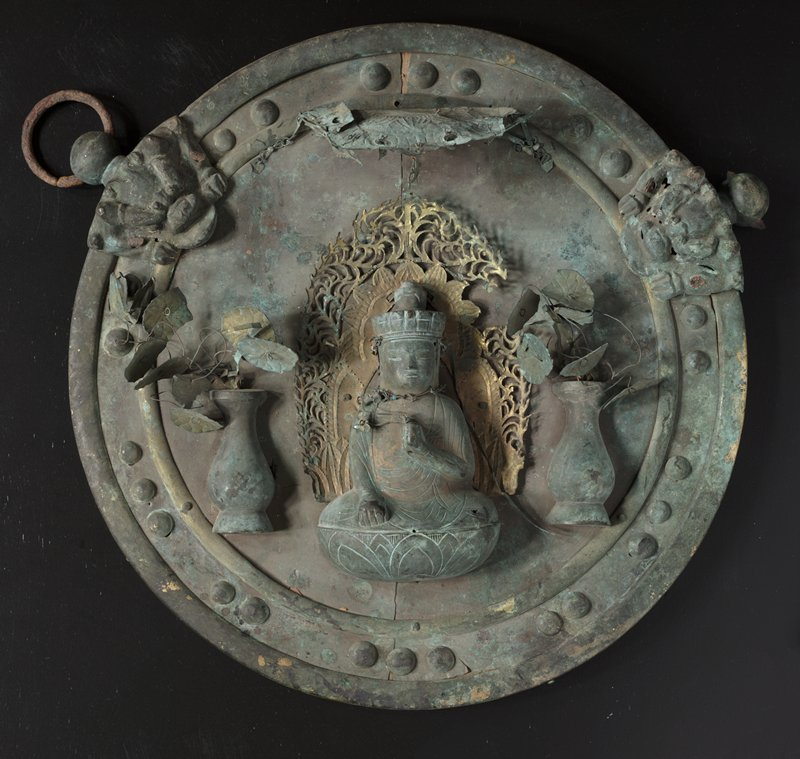 "round bronze disk mounted to wood; raised figure seated on lotus at center, with PR hand resting in lap, and PL hand at heart clutching delicate metal flowers; elaborate golden filigree behind figure; tall urns with delicate wire and bounded metal lotus leaves on either side of figure; thin metal ""awning"" above figure with lotus detail and hanging charms; lion head with claws on either side of top; border with round studs"