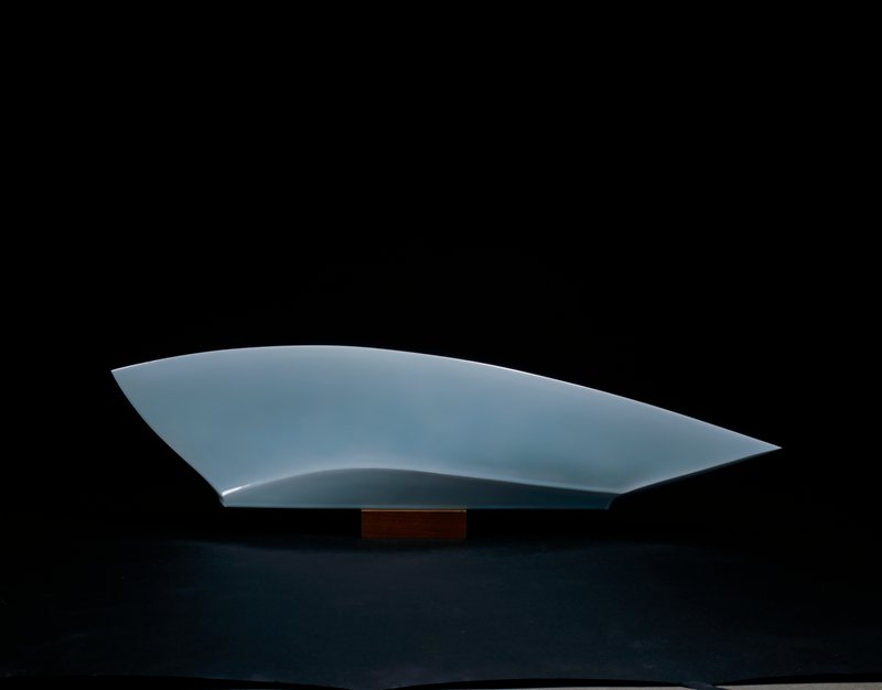 fin-shaped figure with pointed ends; one end is higher, tapering to the end; rests on a wooden block; pale blue-green glaze (seihakuji)