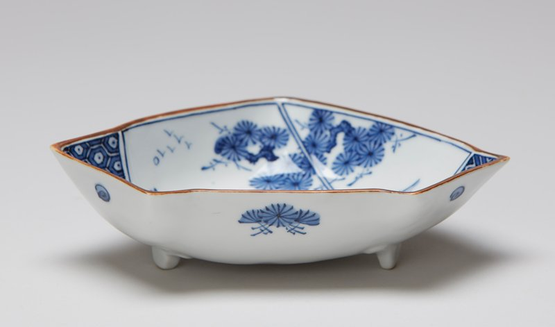 triangular bowl with indented edges on three small feet; bottom corner decorated in blue and white patterns; image of figure in boat between mountains at center; sun with birds in UL and trees UR; floral decoration on sides