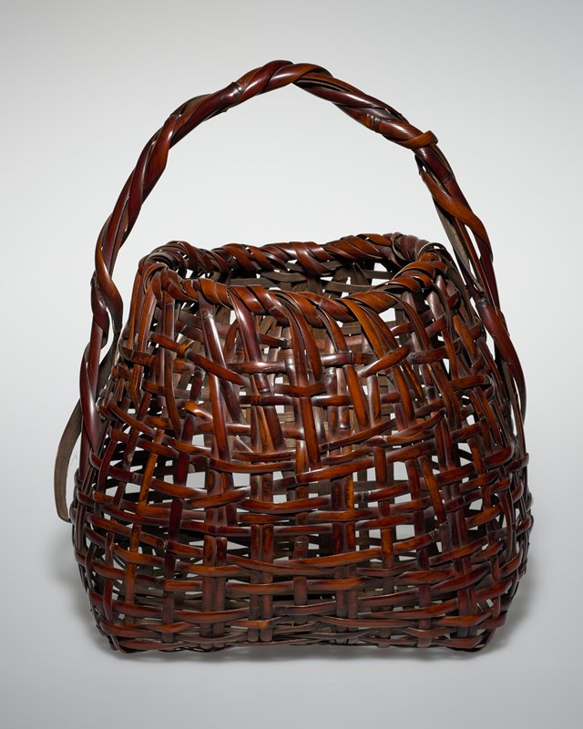 four sided basket with open weave, narrows towards top, round opening; short irregular handle made of twisted strips of bamboo wound over a round piece of bamboo; one twisted strip of bamboo ends in large loop on one side of handle; flower cylinder is reddish-brown lacquered bamboo with ridges, lined with copper