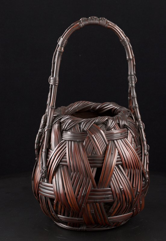 bulbous, squat basket with thick, crisscrossing weave; narrow mouth; slightly lopsided handle made from three bamboo sticks of varying thickness woven together with decorative knots; one side of handle has irregular twig