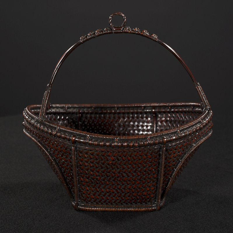 small oval basket with rectangular base; arcing, split handle with loop at top center; decorative knots across handle; woven external supports, with arcing supports at sides; closed weave; copper lined bamboo cylinder