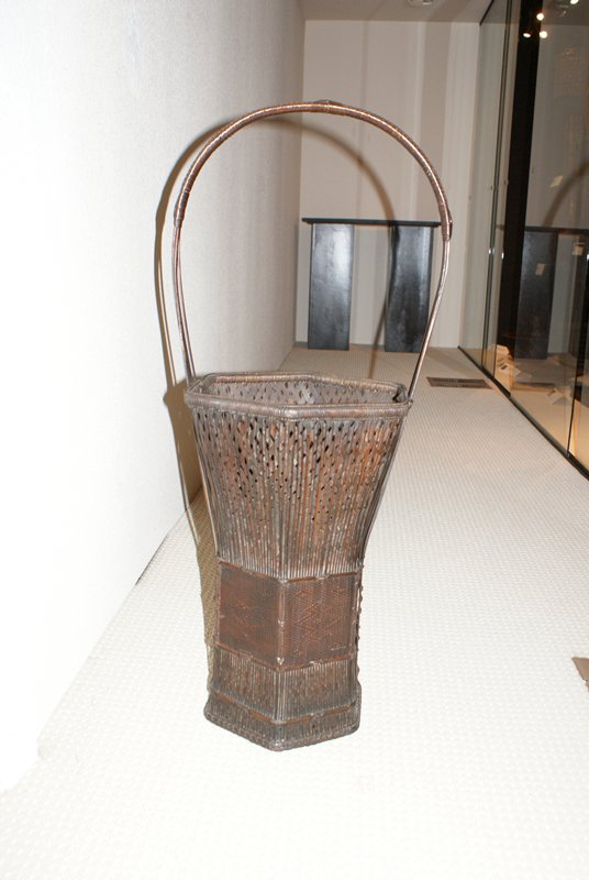 very tall, dark brown hexagonal basket, flares at top; woven with thin, wide strips of rattan in crisscross pattern with thin, vertical strips of rattan loosely overlaid; center decorative band is tightly woven and contains ikat designs; handle base begins near bottom on either side with three narrow strips of bamboo; center strip widens as it arches over the basket, two side strips join and are woven under center strip to form handle; decorative weaving and knots across bamboo handle