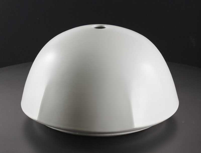 off-white dome-shaped form with flat bottom and small, open mouth at top; subtle flared points near bottom