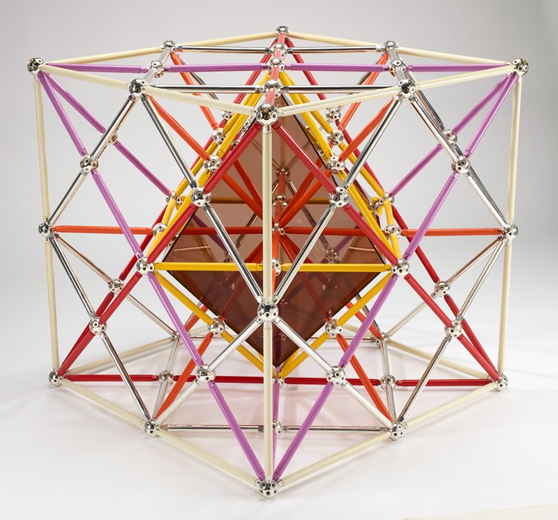 square open cube on openwork base; yellow, purple, red, cream-colored, orange and chrome plastic tubes connected together with metal balls with multiple threaded openings, in the manner of Tinkertoys; smoked Plexi cube in center; received with base disassembled