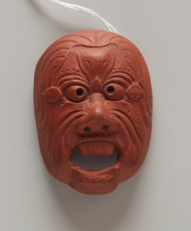 netsuke in the form of a mask; red clay; open mouth with top teeth only (bottom teeth lost); wide nose; beady eyes; leaf-like shapes at outer edges of eyes; wrinkles/lines on cheeks and around eyes