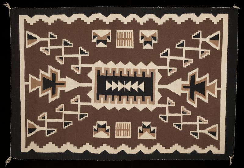 black, cream, and light brown; geometric patterns with triangle motifs at center; stepped cream zigzags around borders