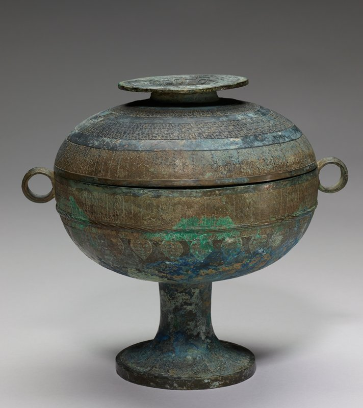 The term Tou for this type of vessel is confirmed by inscriptions. The slightly flattened sphere formed by body and lid appears huge and bulky in comparison with the short, footed stem. When inverted on its shallow disk the lid serves as a separate bowl. This top is adorned with a whorl circle surrounded by squared spirals. The surrounding border is filled with interlaced snakes on a granulation ground. On the lid proper there are three decor belts, separated by bare bands, filled with a minute comma-pattern. The body of the vessel has a similar belt of commas set off by a bare band at the rim and by a narrow rope-patterned band in relief below. There follows a very narrow band of comma pattern above a band of heart-shaped hanging blades filled with commas. the foot, like the disk on the lid, has a belt with interlaced snakes on a granulation ground. The ring-shaped handles have pointed spirals and a rope-patterned band. Patina Grey-green with patches of blue.