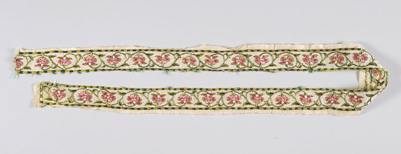 White cotton fabric with embroidered scrolling flowering vine in pinks, white, green and black; border of alternating yellow and green rectangles outlined in black
