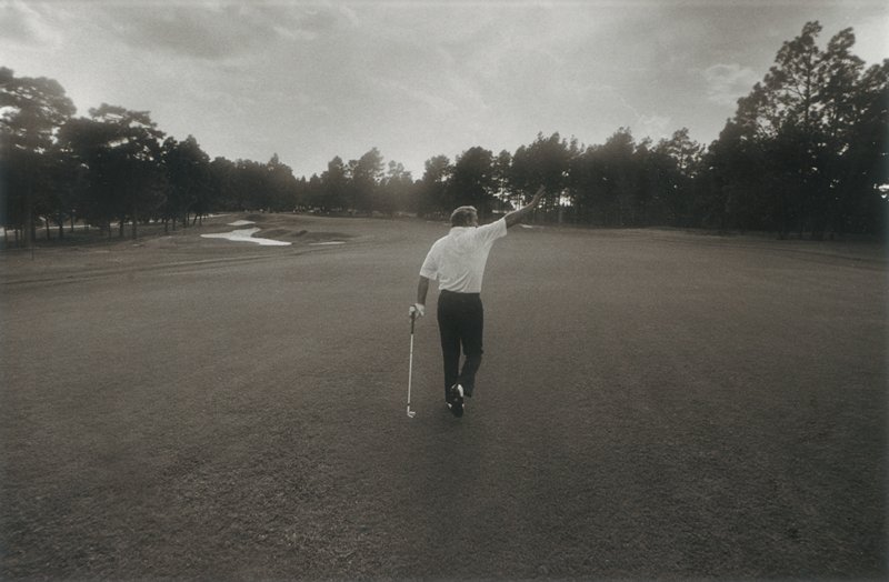man on golf course, seen from back, waving with his PR hand and carrying a golf club in his PL hand, wearing dark pants and a light-colored short-sleeved shirt; trees on horizon line