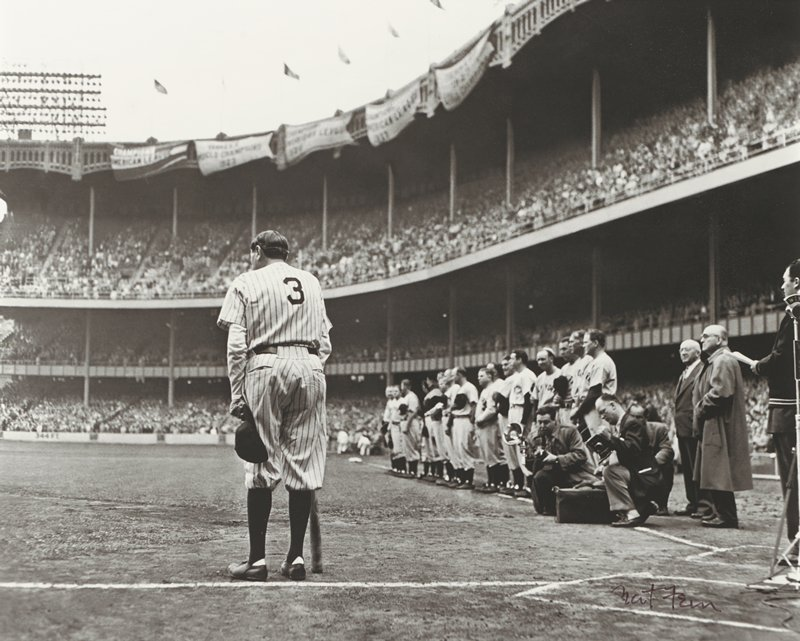 baseball player, wearing #3, seen from back, holding his cap in his PL hand and leaning on his bat held in his PR hand, in a stadium; other baseball players standing in a row at right with photographers and several other men