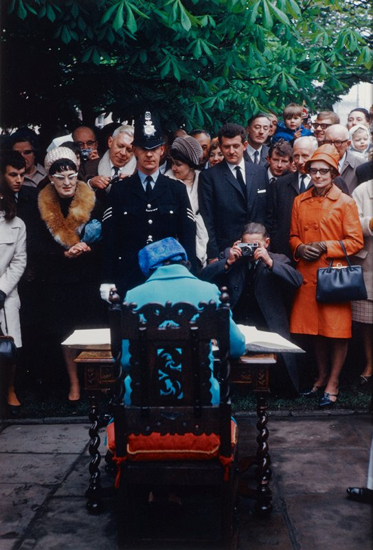 figure seen from back wearing robin's egg blue coat and blue patterned hat, seated in a chair with a carved backrest and red cushion, writing in a large book; crowd observing woman including police officer, crouching photographer and woman in orange coat and hat in front row; foliage above crowd