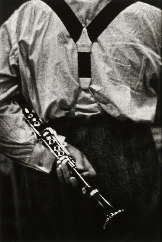 torso of man seen from back wearing suspenders, dark pants and light-colored shirt, holding a clarinet across his PL arm across his back