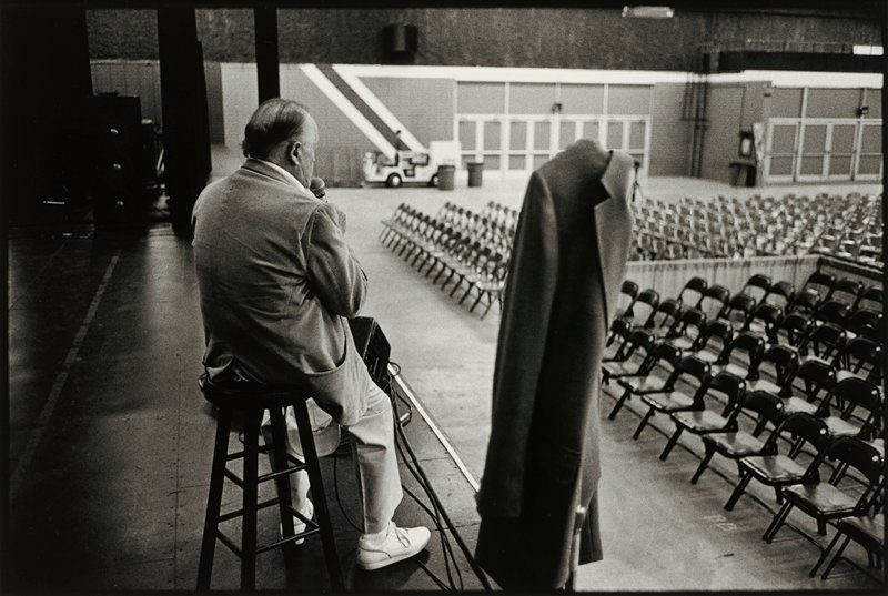 elderly man turned 3/4 to PR, seated on a stool on a stage, holding a microphone; man wears white tennis shoes; suit jacket hanging on microphone stand at center; rows of folding chairs at right