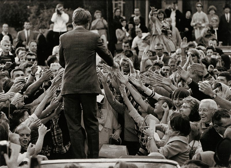 man wearing suit seen from back reaching toward the outstretched hands of a crowd of people below him