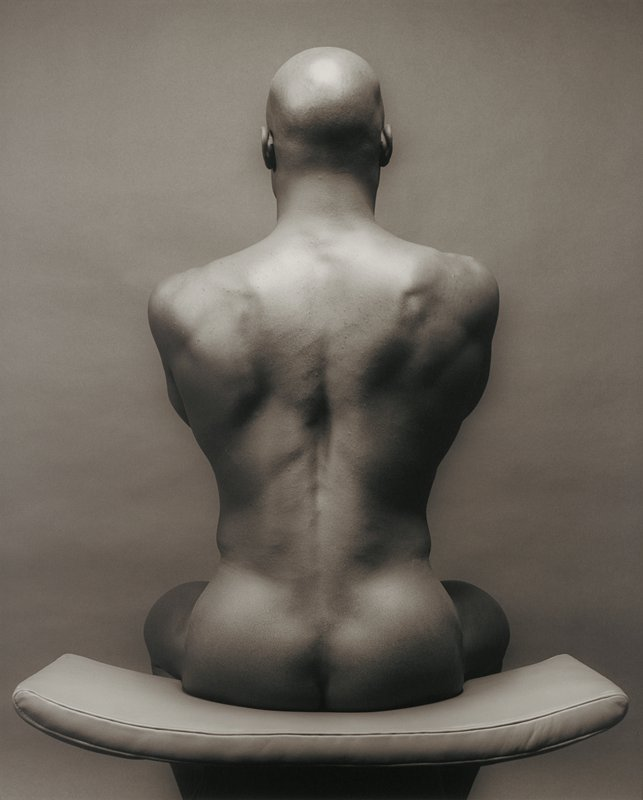 back view of a nude black man seated on a curved leather stool
