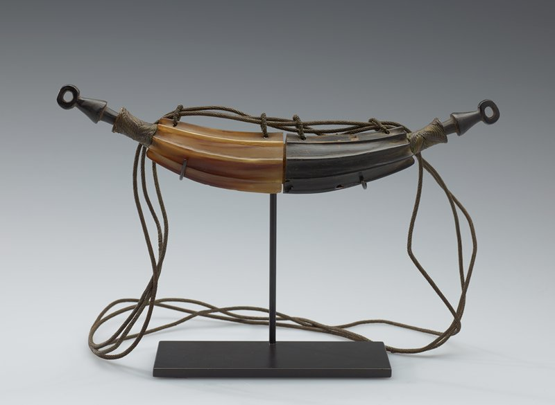 banana shaped container made of ribbed horn, one half light and one half dark in color; stopper in each end; ends of body of container and three straps made of woven brass (?) wire; stoppers are dark in color with an open circular shape at the ends; black mount