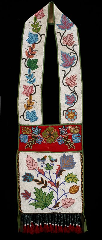 shoulder bag with wide strap with beaded twining vine with multicolored leaves against a white beaded background, with green wool trim at edges; top of bag is red wool decorated with symmetrical floral beading; body of bag decorated with multicolored leaf design with two small birds at top, facing one another, against a white beaded ground; dark green and white beads and maroon wool tassels on fringe at bottom