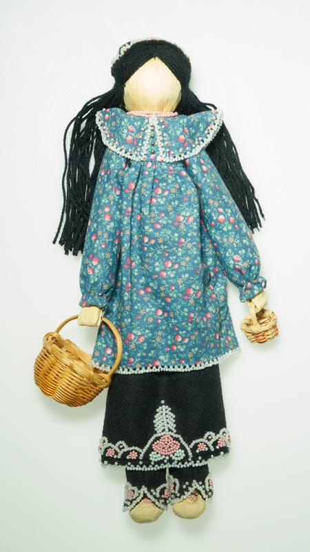 "standing faceless doll with long black yarn hair; doll wears a flowered tunic blouse with blue ground and tiny orange and pink flowers, with white beading at hem and cuffs, and white and pink beads around collar; silver bead ""buttons"" at top front; black wool shin covers with black wool skirt; skirt and shin covers are decorated with pink, pale green and white beads in floral motifs; leather moccasins decorated with pink and pale green beads in floral motifs; two strands of pink beads around neck; doll holds a tiny pink and light tan basket; doll has a black wool crown-like hat deocrated with pink and white floral motif beading; another similar larger basket accompanies doll"