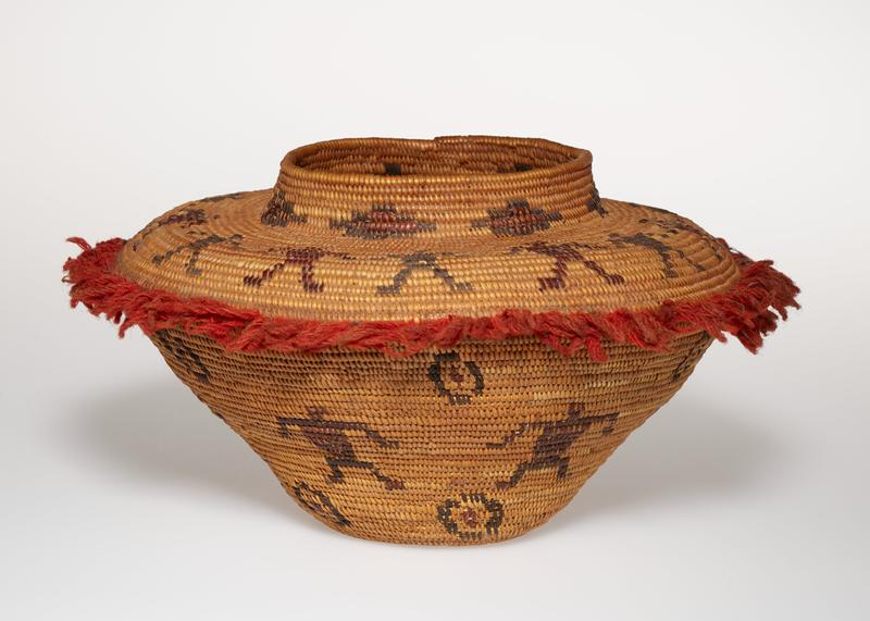 coiled basket; small foot with outward-flaring sides and wide, rather flat shoulder; short neck with wide mouth opening; red yarn fringe at point of shoulder; light brown with dark brown band of figures on shoulder and body; band of stepped diamonds on neck; repeating circular motifs above and below figures on body