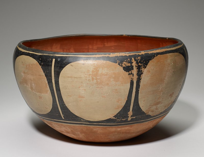 heavy bowl with thick base; flat bottom; rounded sides with inward-flaring rim; rust red interior and bottom; band around body is black with cream-colored circles separated by vertical cream-colored bars