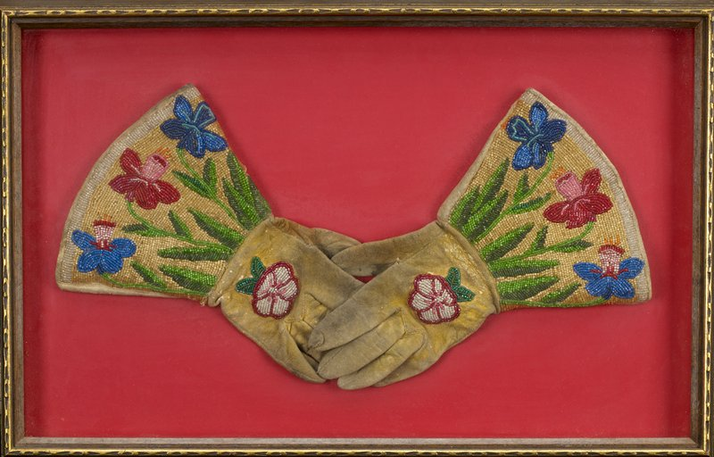 pair of gloves with wide gauntlets on each wrist; beaded pink, red and white flower blossom on back of each hand; two blue and one red daffodil-shaped flowers with green stems and leaves in beads on each wrist; light tan leather; received mounted together and framed