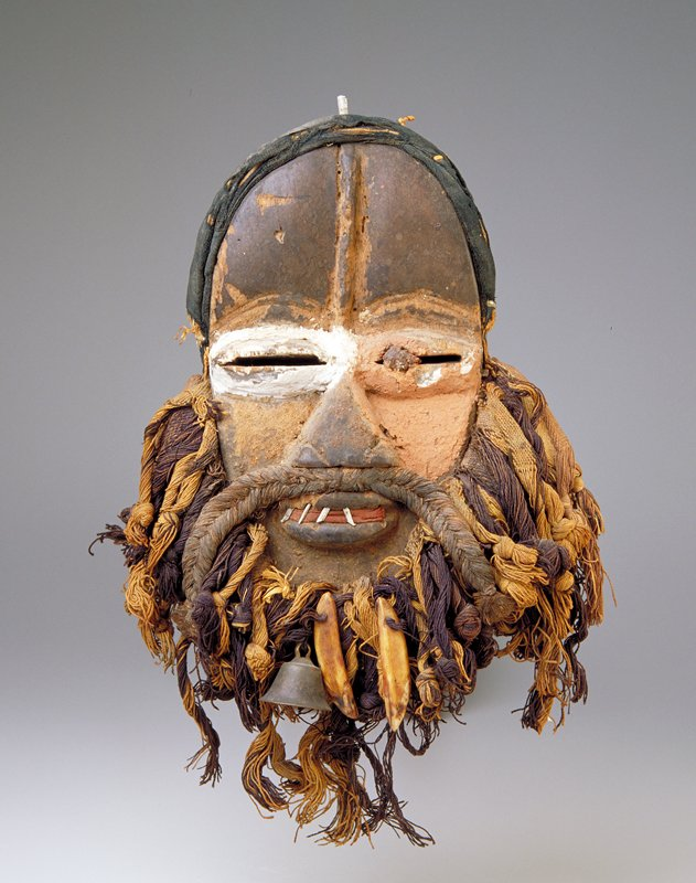 Flat face; narrow eyes with proper right eye in white and proper left eye and cheek in terra cotta color; metal rods for teeth; beard and moustache braided and twisted brown and tan threads; metal bell and 2 ivory 'teeth' at center of beard