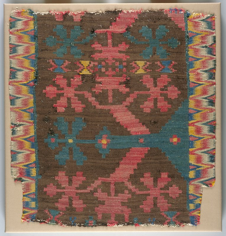 Wool tapestry weave; geometric/floral shapes in blue, yellow and red on brown; zigzagged border in red, blue, yellow, white and green; mounted