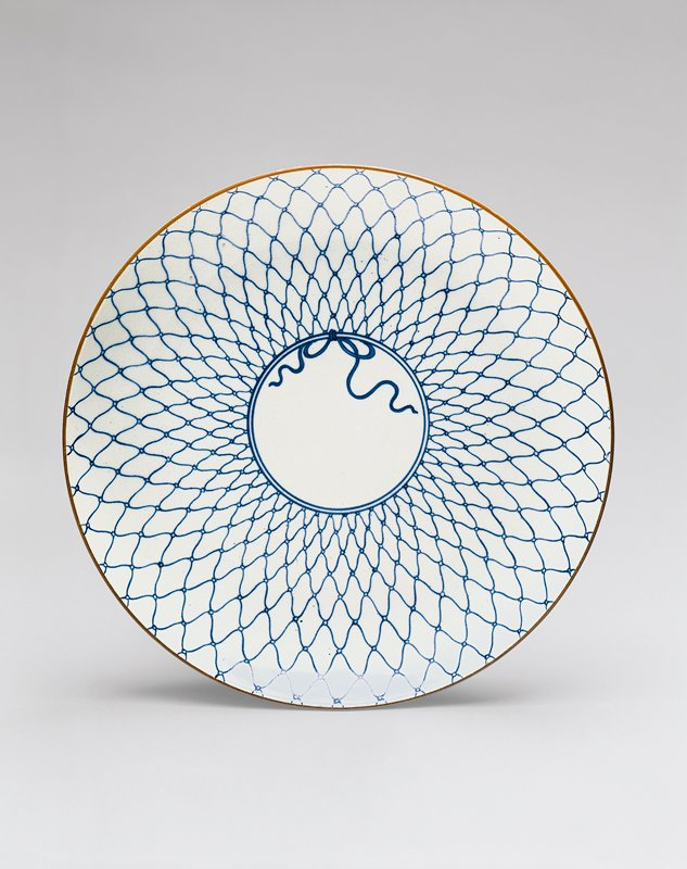 shallow white porcelain dish with fishnet design; drawn closed in a circle around center of dish with bow; scrolling vine design on underside
