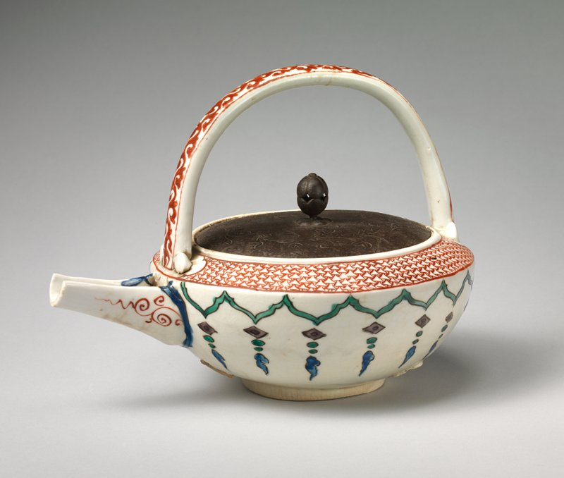 small ceramic pot with metal lid; ceramic handle with stylized red vine design; red and white geometric pattern around neck; open spout; green zigzagging design below neck with vertical trailing designs of diamonds and puffs in purple, green, and blue; lightly incised floral motif on lid